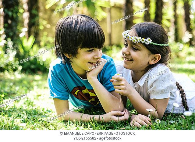 Portrait of little girl with crown of daisies, and child t-shirt with superman, lying in the grass