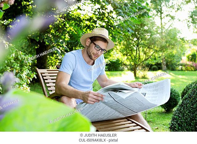 Mid adult man reading newspaper in garden