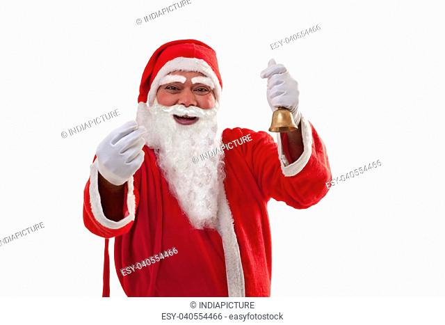Portrait of cheerful Santa Claus gesturing while holding bell over white background