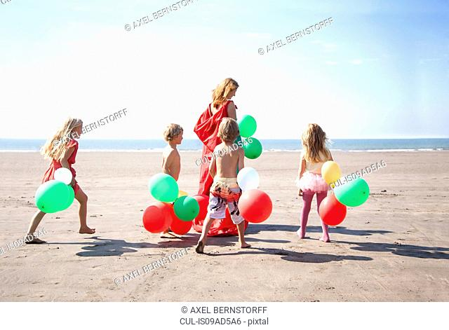 Mother with four childen on beach with balloons, Wales, UK