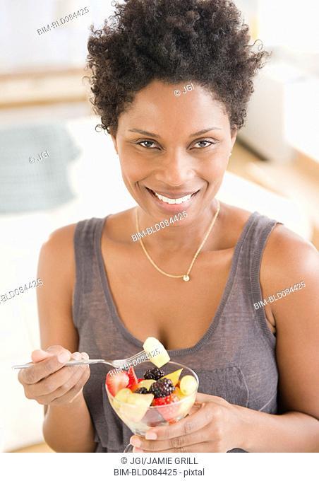 Black woman eating fruit salad