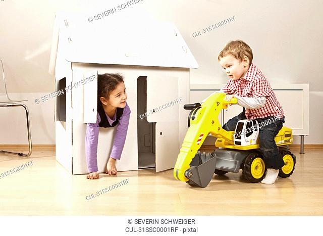 Boy and girl in front of cardboard house