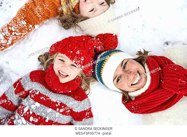 Mother and daughters lying on snow, having fun