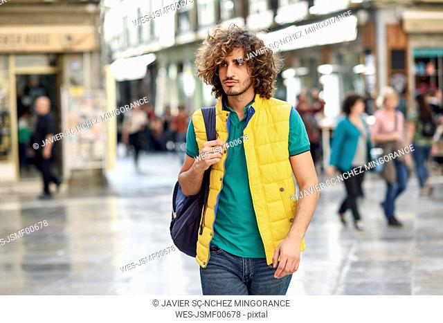 Spain, Granada, portrait of young tourist with backpack discovering the city