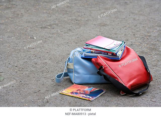 School bags and books on ground