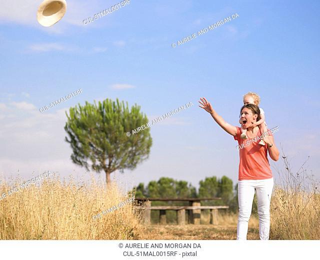 Wind blowing womans hat in field