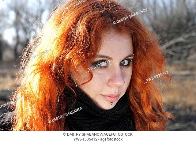 red haired girl outdoors headshot