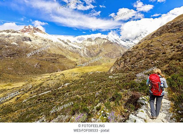 Peru, Andes, Cordillera Blanca, Huascaran National Park, tourist on hiking trail with view to Nevado Huascaran and Nevado Yanapaccha