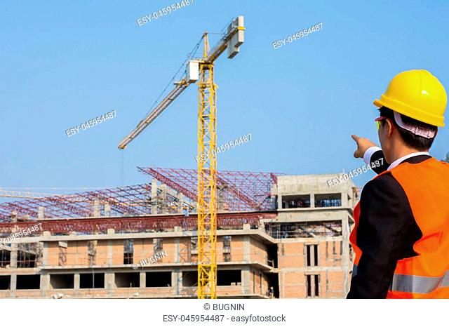 Young engineer in orange shirt stands pointing at a building being built with a crane