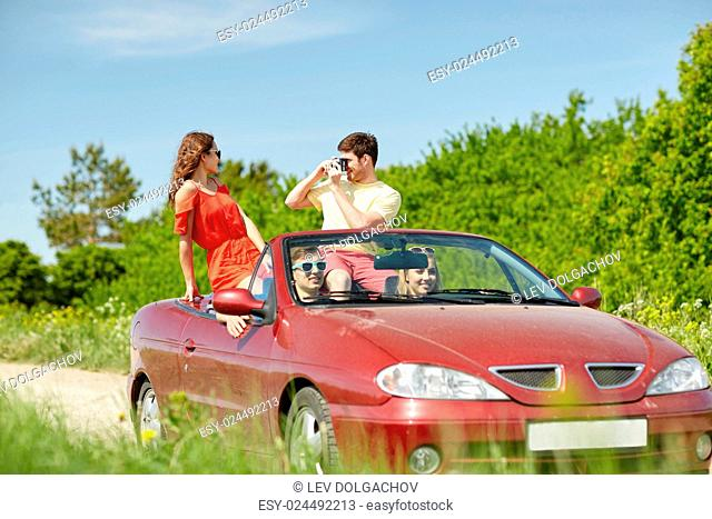 leisure, road trip, travel, summer holidays and people concept - happy friends driving in cabriolet car and taking picture by film camera