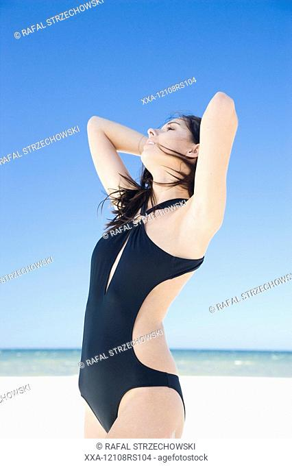 woman on beach in black swimming suit