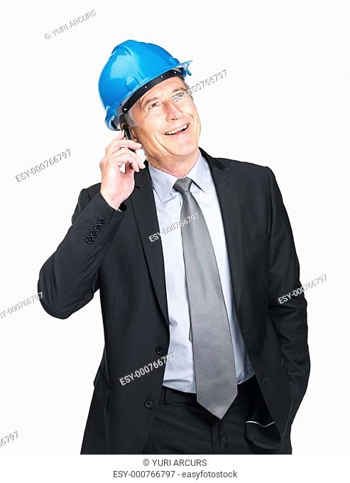 Happy old construction worker speaking on cell phone on white background