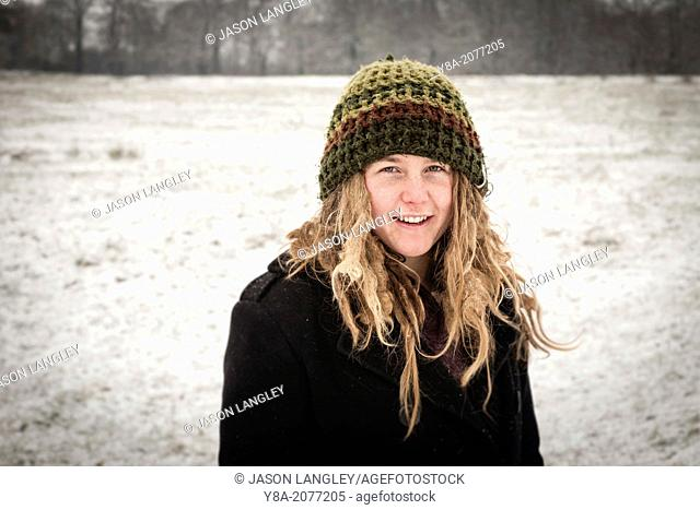 Young woman with dreadlocks wearing a knit hat in the snow, Creuse Department, Limousin, France
