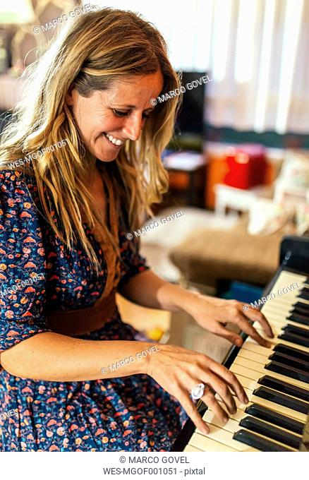 Smiling woman playing piano