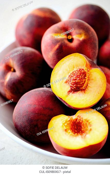 Bowl of whole and half peaches