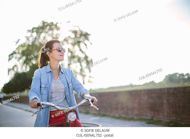 Mid adult woman pushing bicycle on rural road, Tuscany, Italy