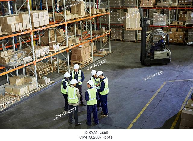Workers meeting in a circle in distribution warehouse