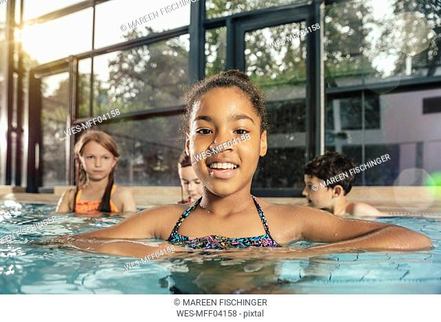 Portrait of smiling girl with friends in indoor swimming pool