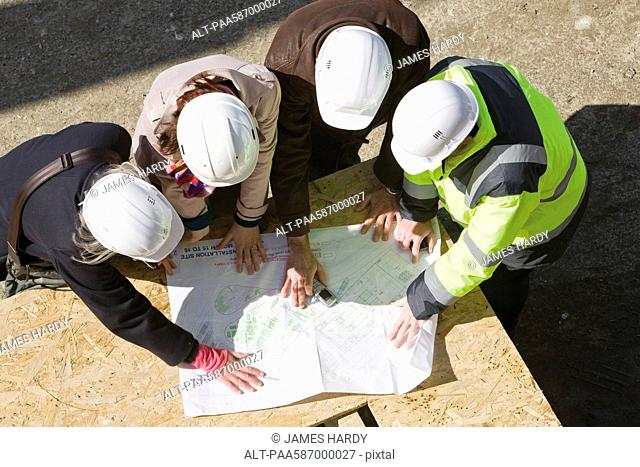 Architects meeting with building contractor at construction site to review blueprints