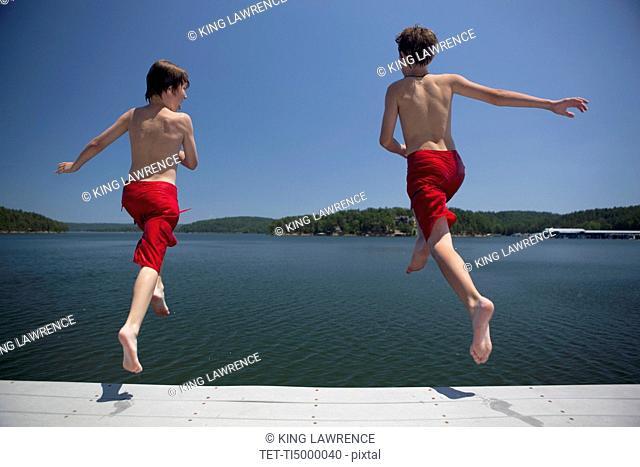 USA, Arkansas, Murfreesboro, Two brothers 8-9, 12-13 jumping into water