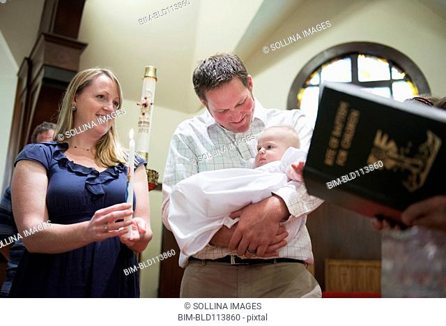 Caucasian parents having baby baptized in church