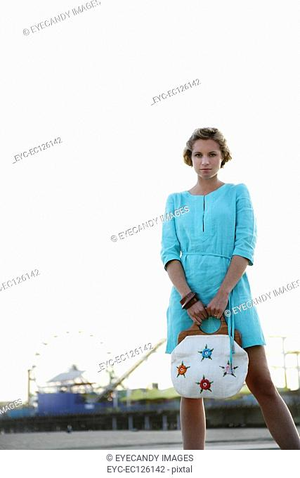Portrait of young woman with handbag standing in front of amusement park