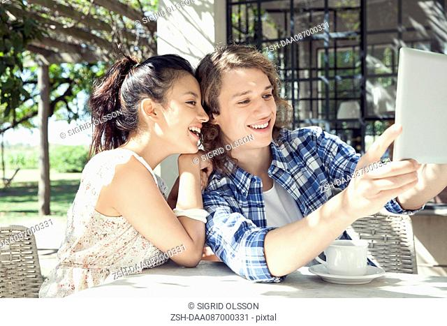 Young couple taking selfie with digital tablet