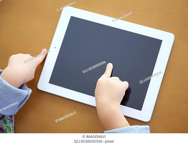Girl's hands touching a tablet PC