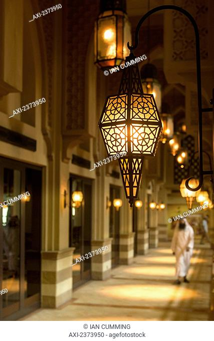 Man in traditional arabic dishdasha outfit walking along corridor in shopping mall; Dubai, United Arab Emirates