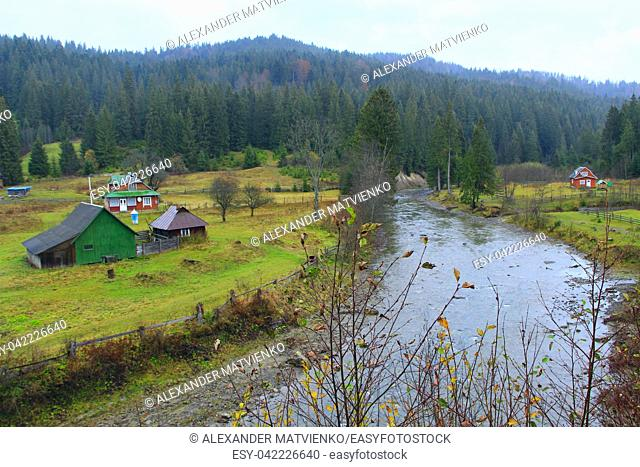 landscape with mountainous river flowing in Ukrainian village in forest of Carpathian mountains