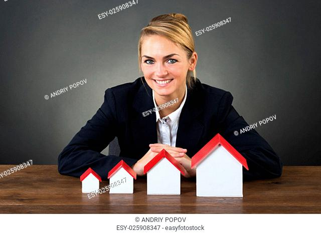 Portrait of smiling businesswoman with model houses arranged in graph order at desk