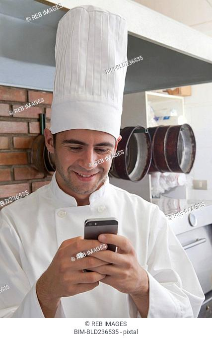 Smiling Hispanic chef texting on cell phone