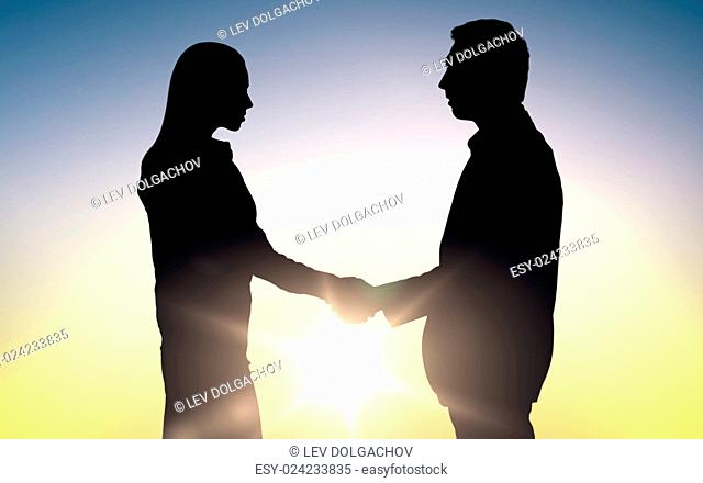 business, teamwork, partnership, cooperation and people concept - business people shaking hands standing over sun light background
