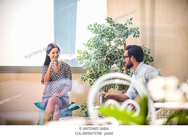 Couple talking and drinking mint tea on hotel room balcony, Dubai, United Arab Emirates