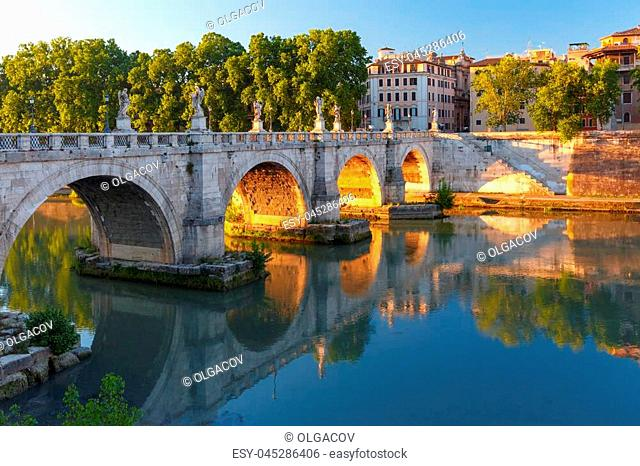Saint Angel bridge with mirror reflection in Tiber River at sunset in Rome, Italy