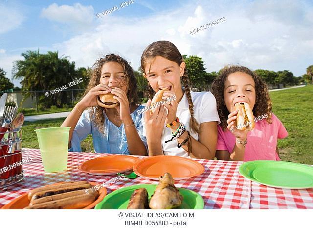 Hispanic girls eating at picnic table