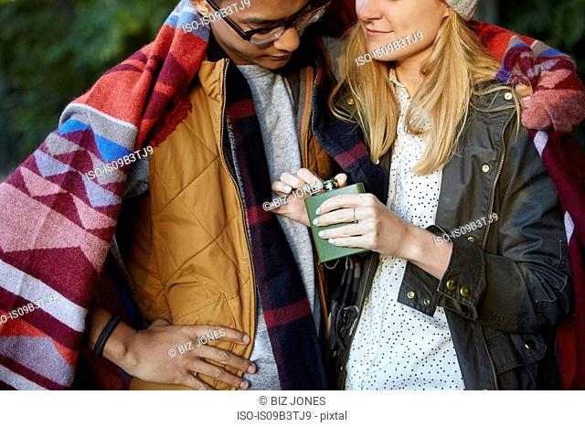 Cropped shot of couple wrapped in blanket, opening hip flask in park