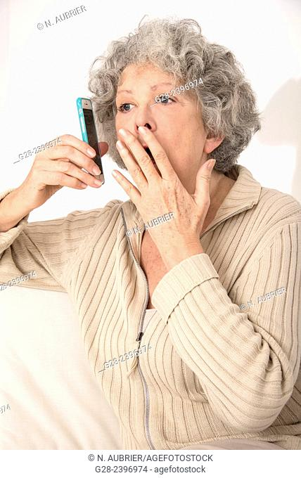Beautiful surprised senior woman on the phone with hand in front of her mouth