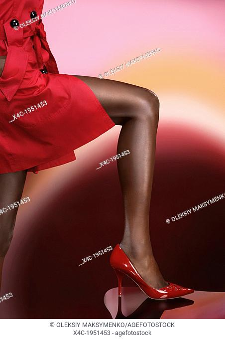 Closeup of a sexy black woman leg wearing a red high heel shoe isolated on colorful background