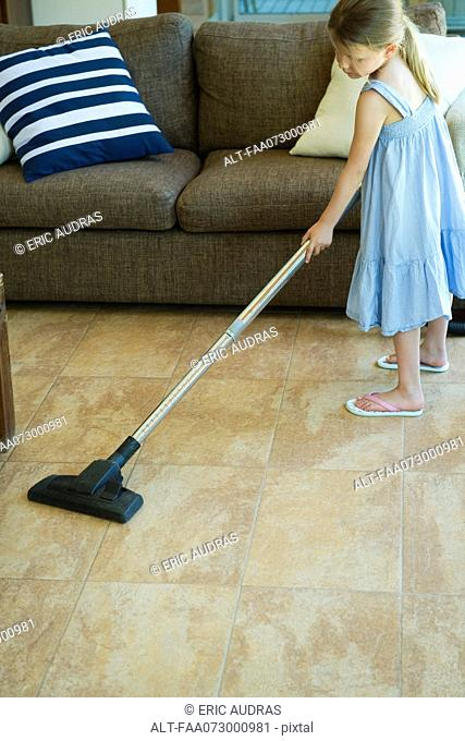 Little girl cleaning living room floor with vacuum cleaner