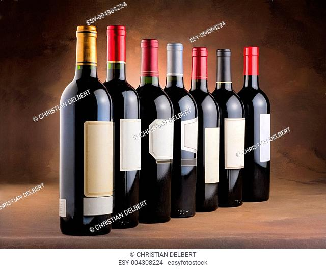 Red wine bottles lined up in a row with blank labels