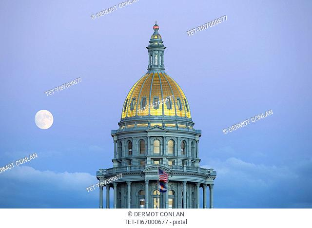 USA, Colorado, Denver, Full moon rising next to State Capitol dome