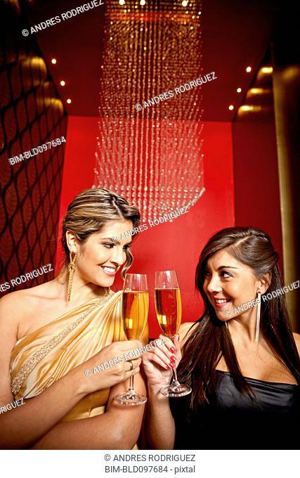Glamorous Hispanic women toasting with Champagne