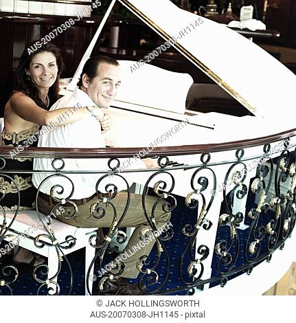 Portrait of a mid adult man playing a piano with a mid adult woman smiling beside him