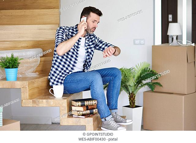 Displeased man moving into new flat talking on cell phone checking the time