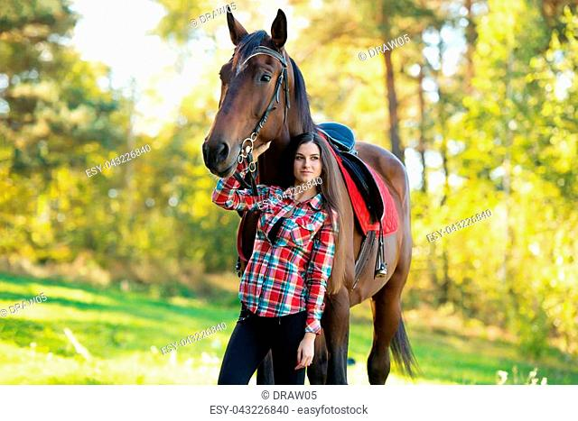 beautiful young woman with a brown horse on outdoor. Autumn landscape