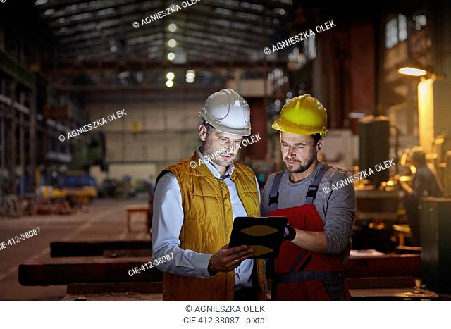 Male foreman and engineer using digital tablet in dark factory