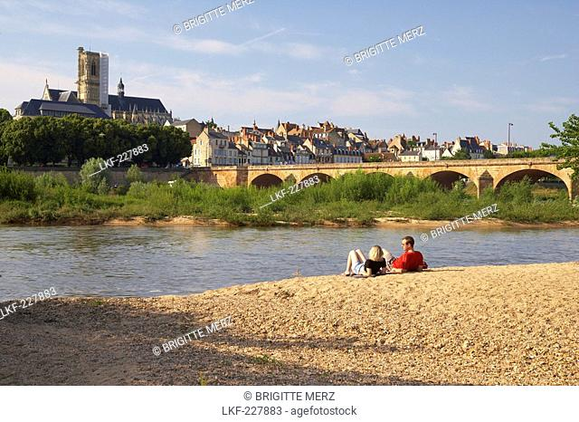 Young couple sitting along the banks of the river Loire, Saint Cyr et Sainte Julitte Cathedral in the background, Bridge over the river Loire, The Way of St