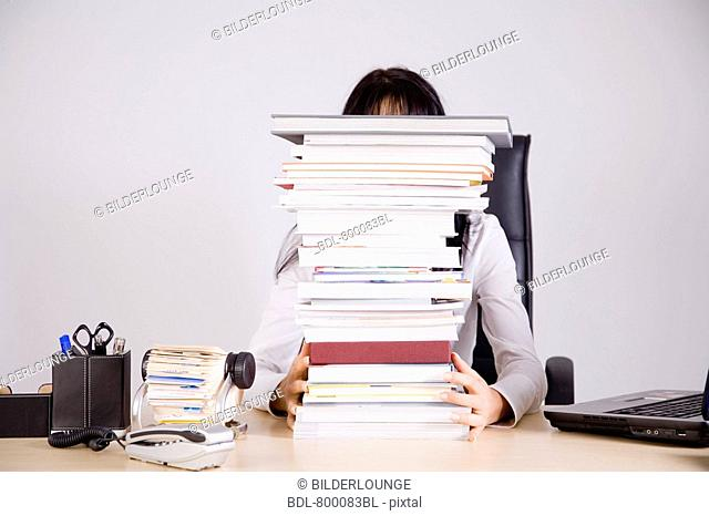 businesswoman sitting on desk hidden behind pile of books