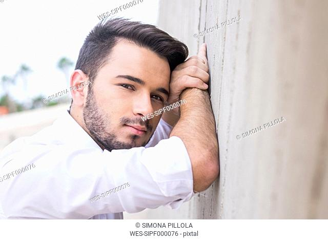 Portrait of young businessman leaning against wall
